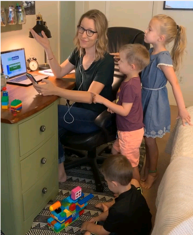 Lindsay in her home office being visited by her three children.