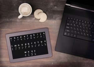 Braille on a tablet next to keyboard